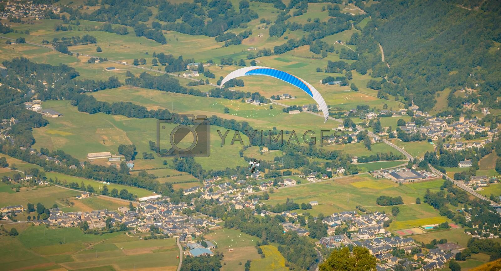 Saint Lary Soulan, France - August 20, 2018: paragliding in flight at the top of the mountain at 1700 meters above sea level flying over the valley on a summer day