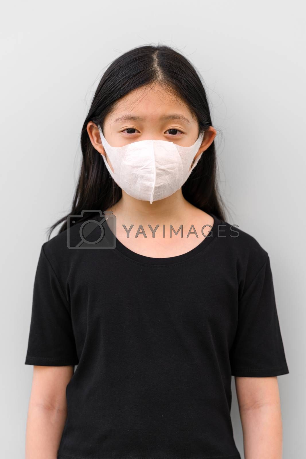 Front view of Asian child wearing mask protecting herself from COVID-19 or Corona Virus.