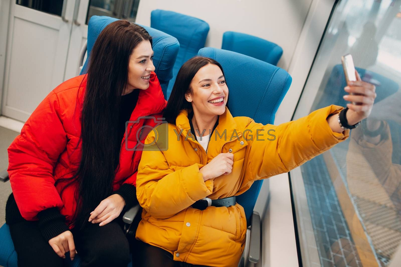 Two young women take a selfy shot with mobile phone in train