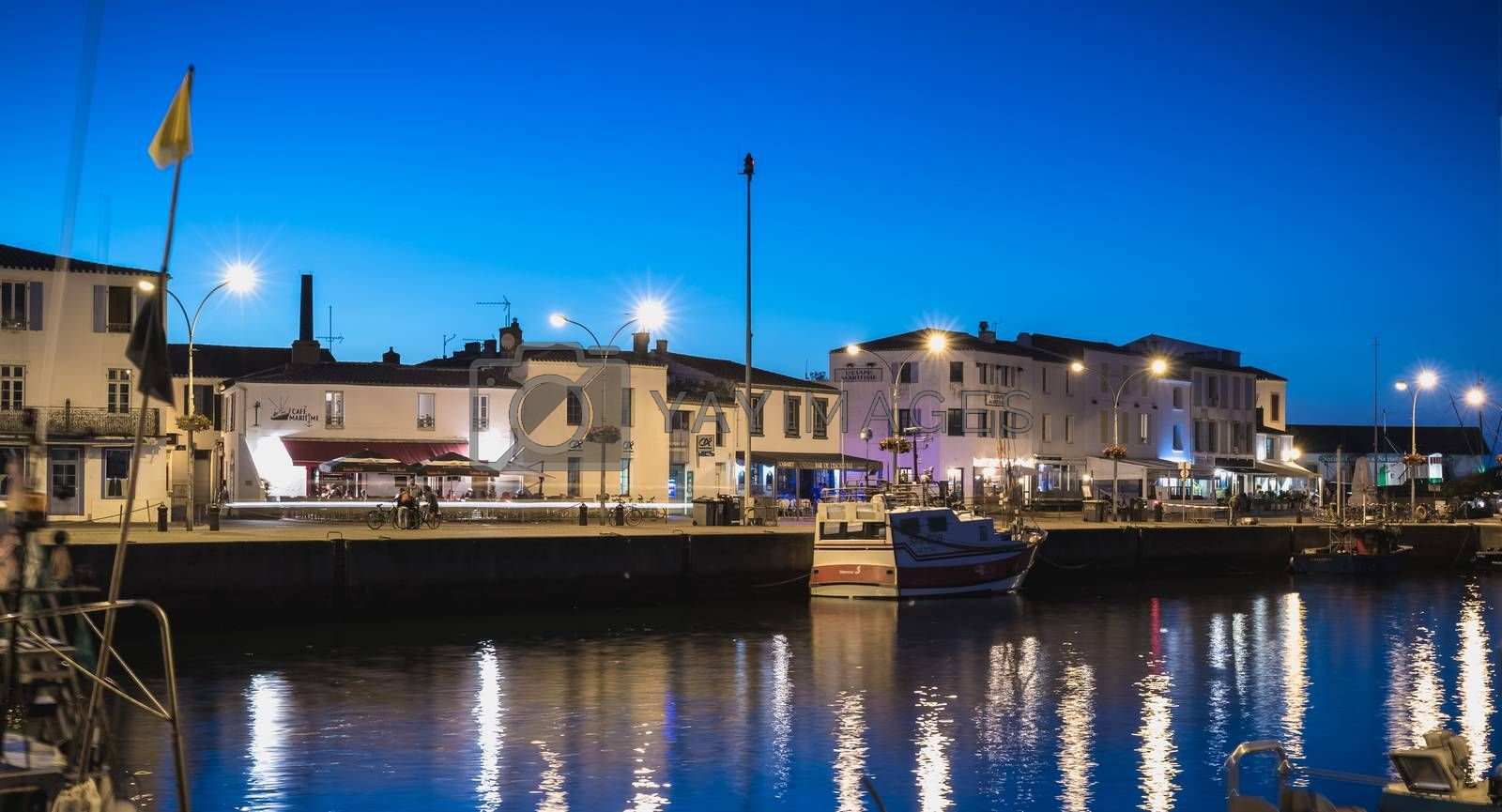 Port Joinville, France - September 19, 2018: view of the main port of the Yeu island with its picturesque architecture and its fishing boats at night on a fall day