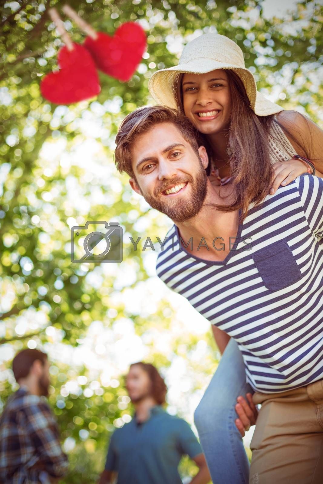 Hipster couple having fun together against hearts hanging on a line