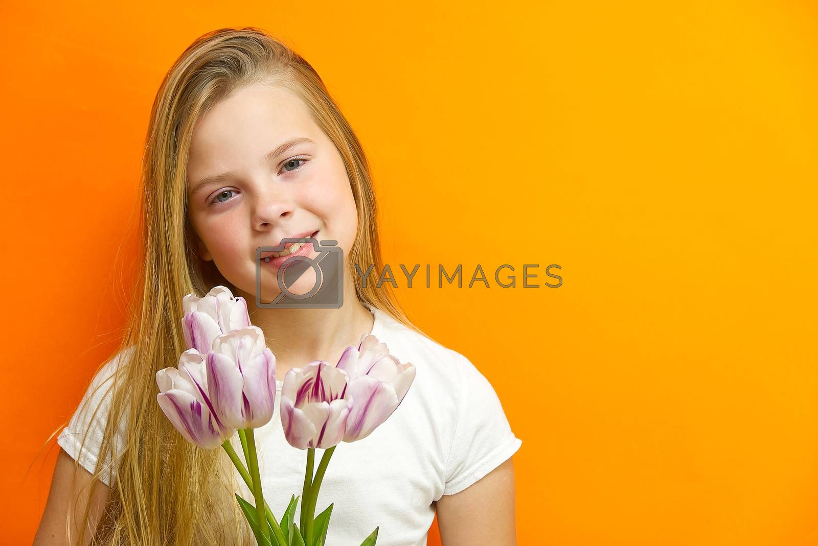 smiling young handsome girl on an orange background with tulips in hands. Children happiness