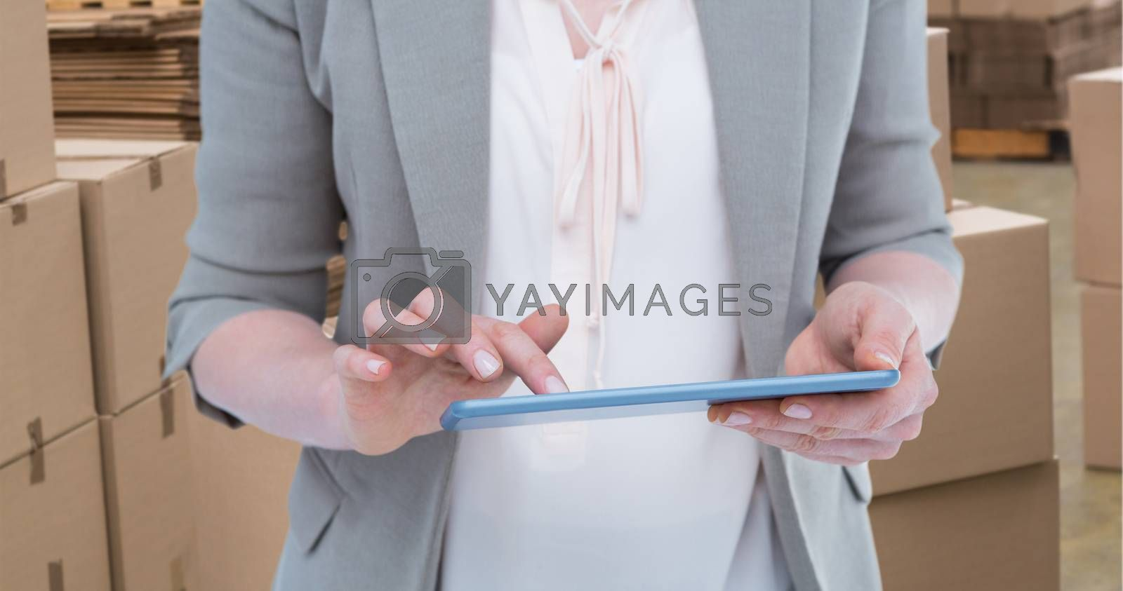 Close up of woman using tablet against preparation of goods for dispatch