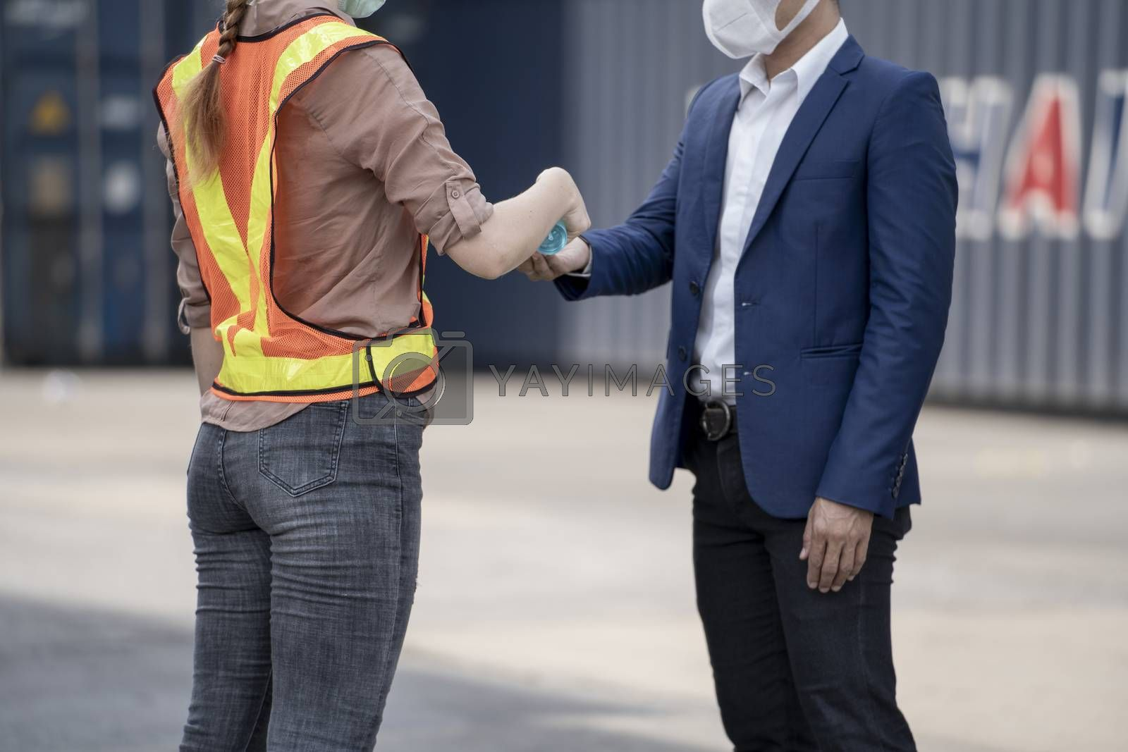 Factory woman worker in a face medical mask and safety dress using alcohol gel for hand cleaning to protect coronavirus disease at outdoor factory warehouse at worker people standing on queue. Background of cargo container warehouse.