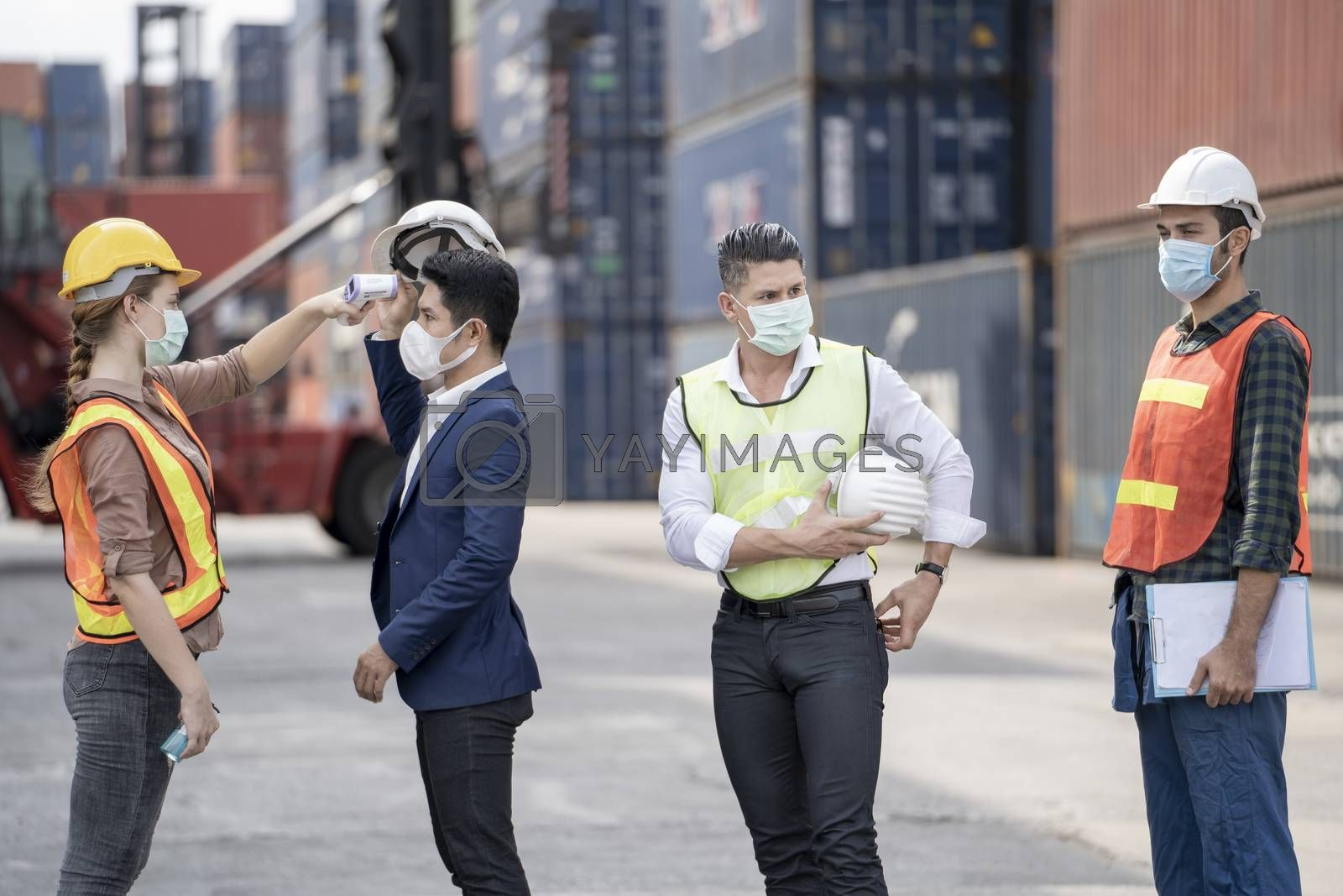 Factory woman worker in a face medical mask and safety dress used measures temperature at worker people standing on queue with a non-contact infrared thermometer.
