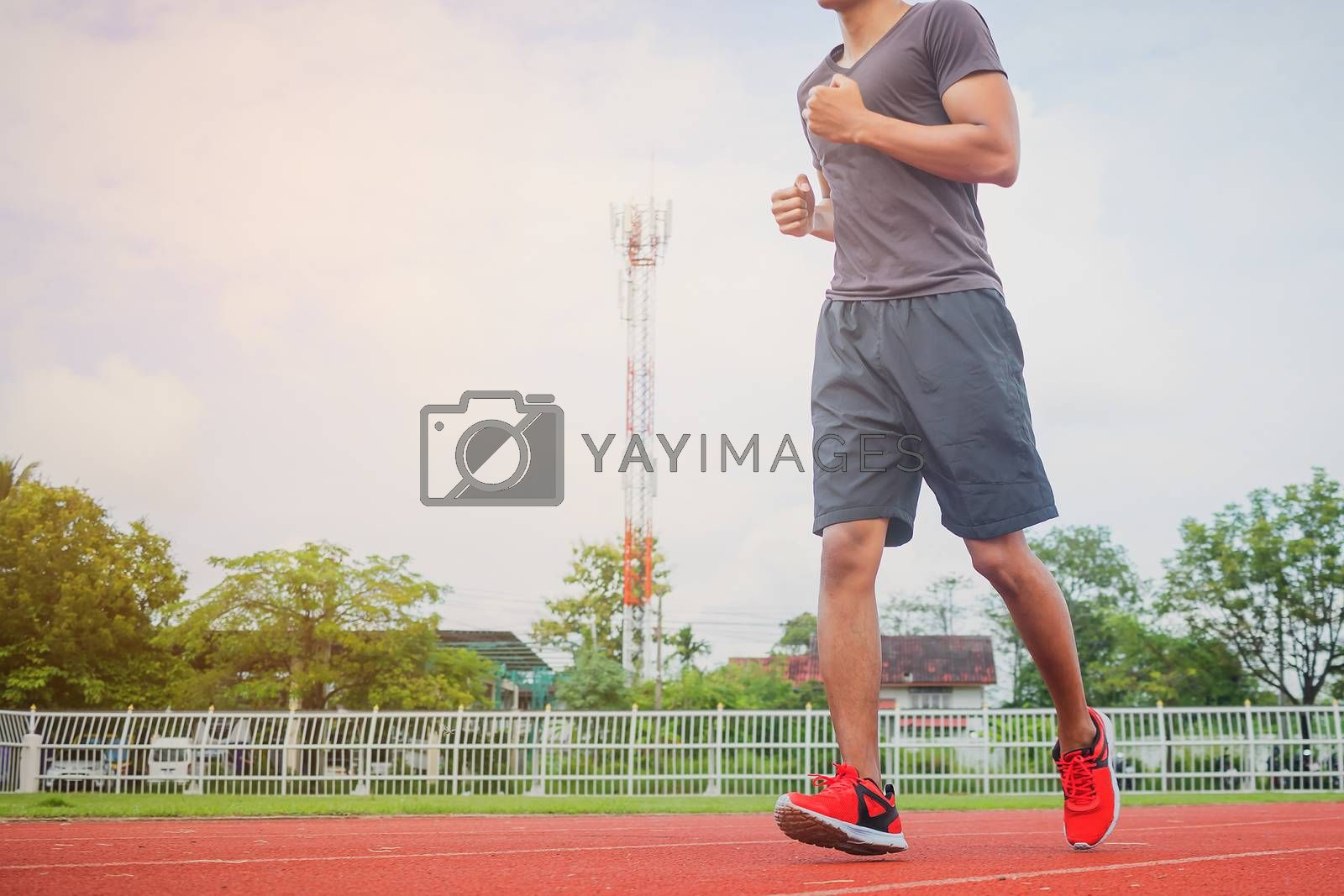 Young man jogging in the morning sun in the stadium.