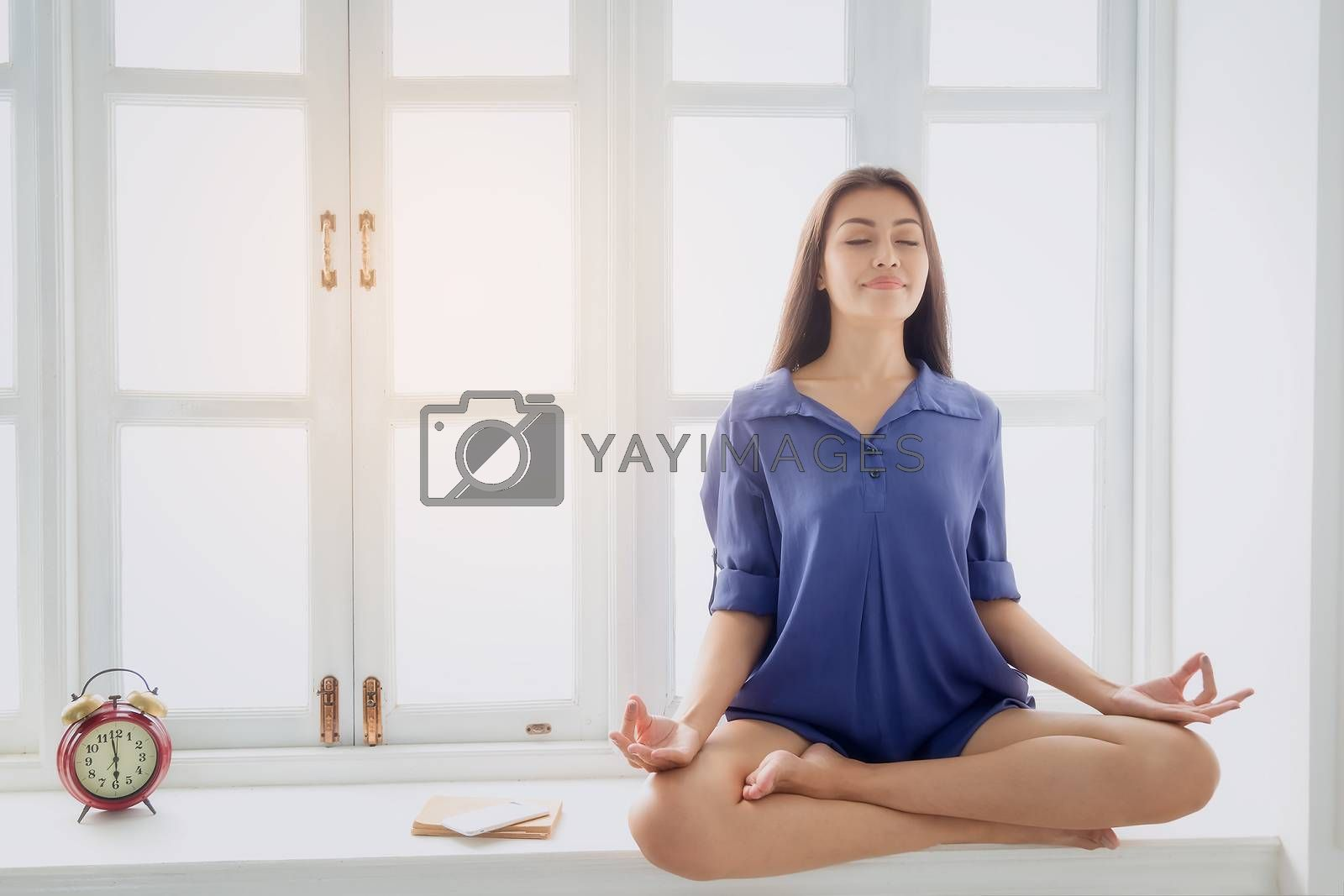 Young woman exercises with yoga in the morning after waking up. Health care concept
