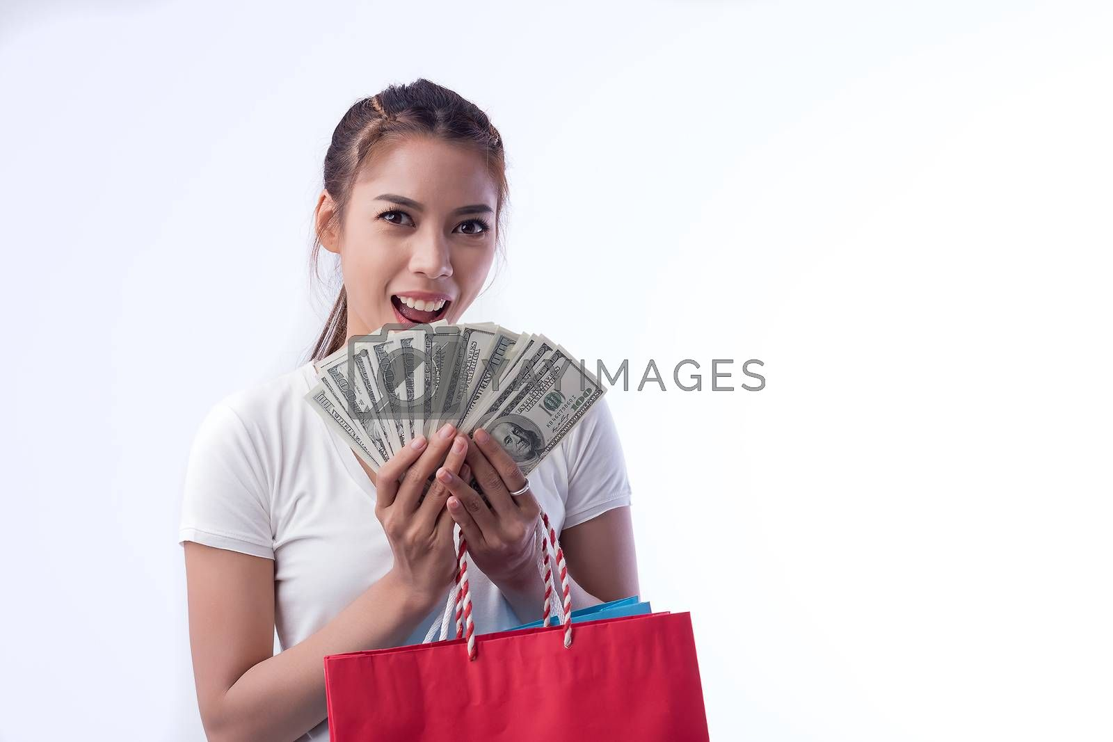 Picture of a beautiful black haired girl in a summer dress, holding a dollar bill with a shopping bag, and looking at the camera through a white background.
