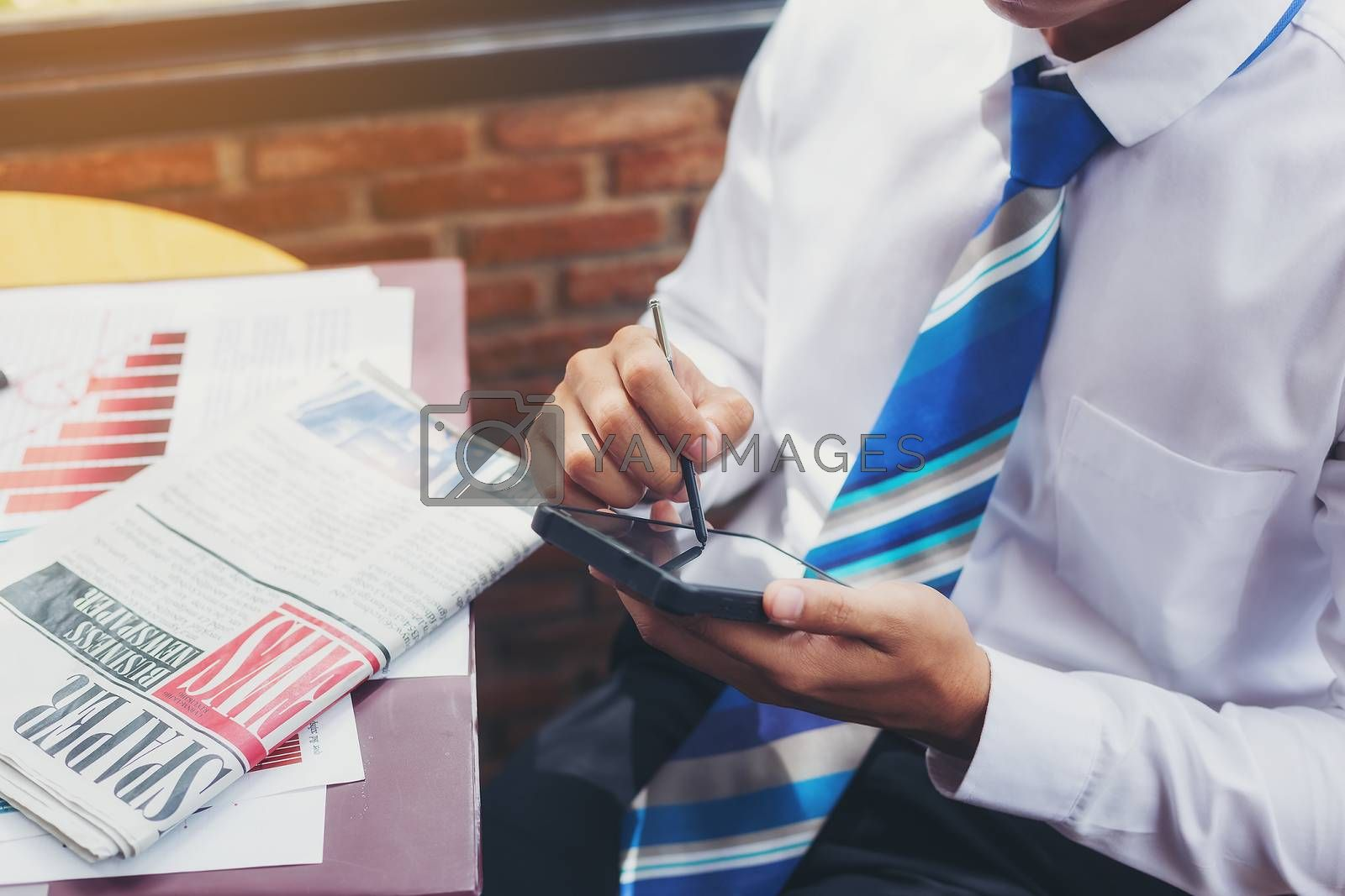 A handsome businessman reading a text from a mobile phone while sitting in a coffee shop.