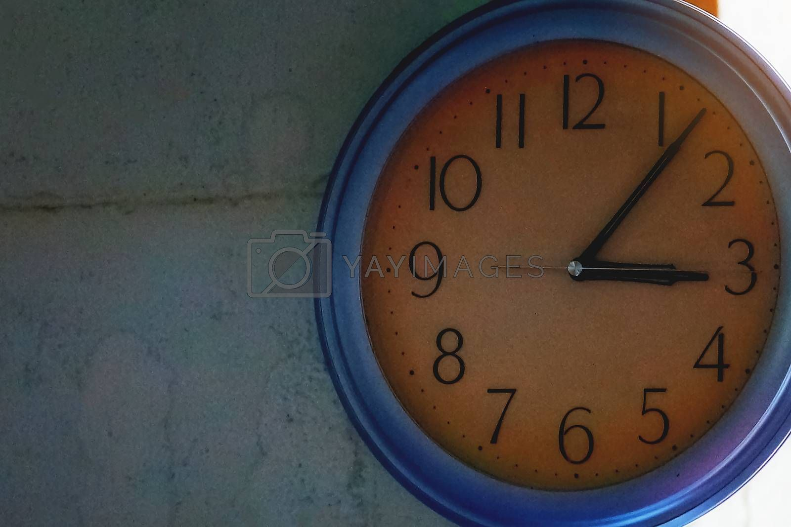 Yellow floor clock on blue cement wall