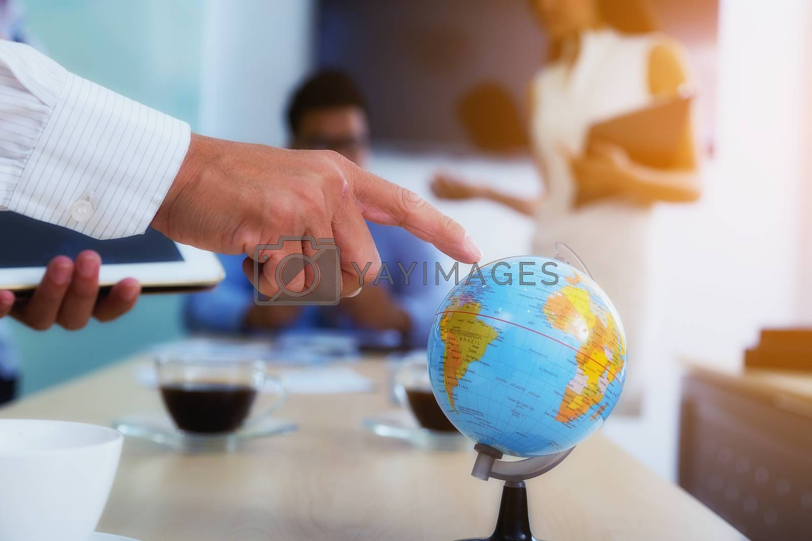 Portrait of businessman pointing his finger at the globe to determine a business investment point with a backdoor is a meeting.
