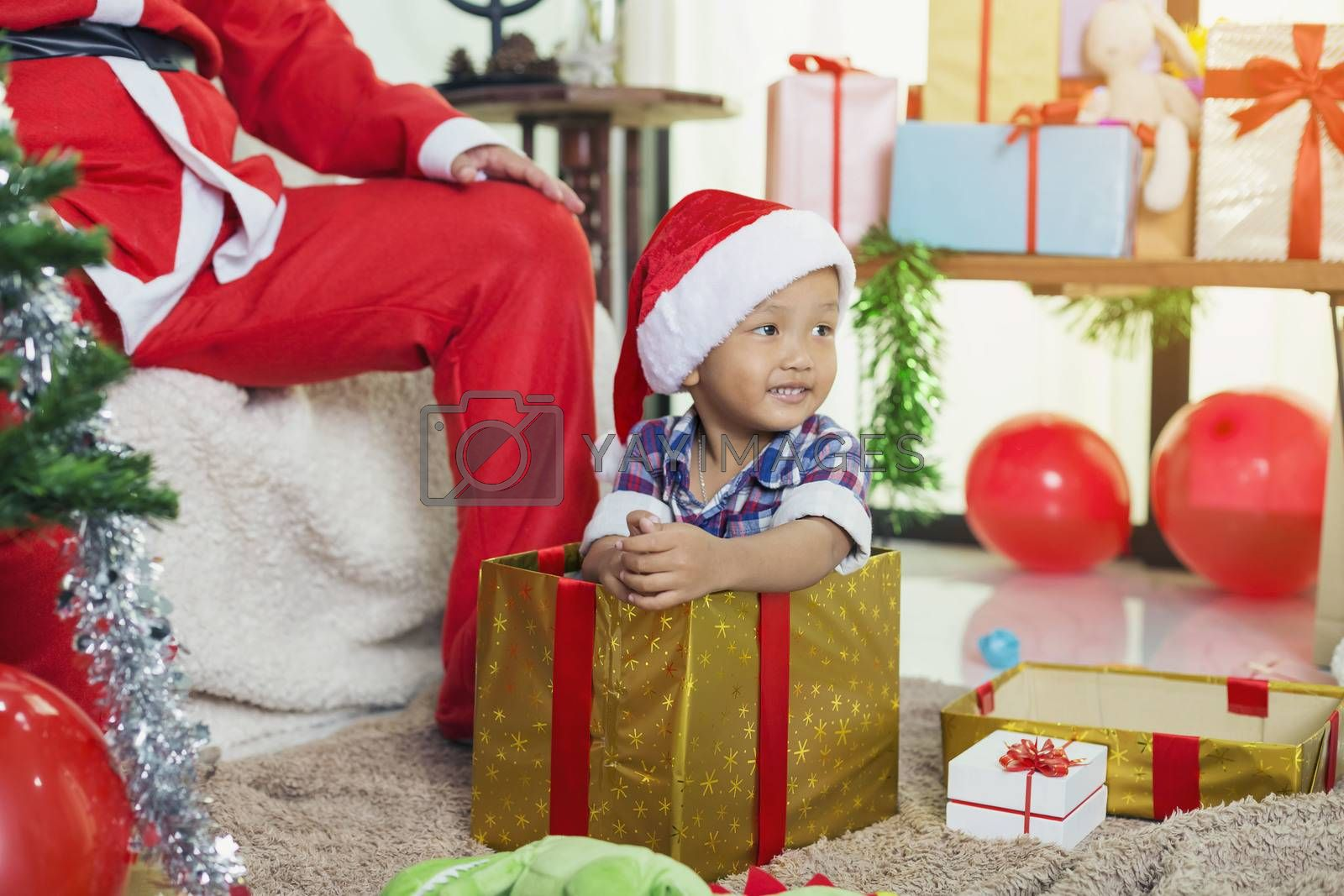 Santa Claus opens a gift box with little boy sitting in a box.