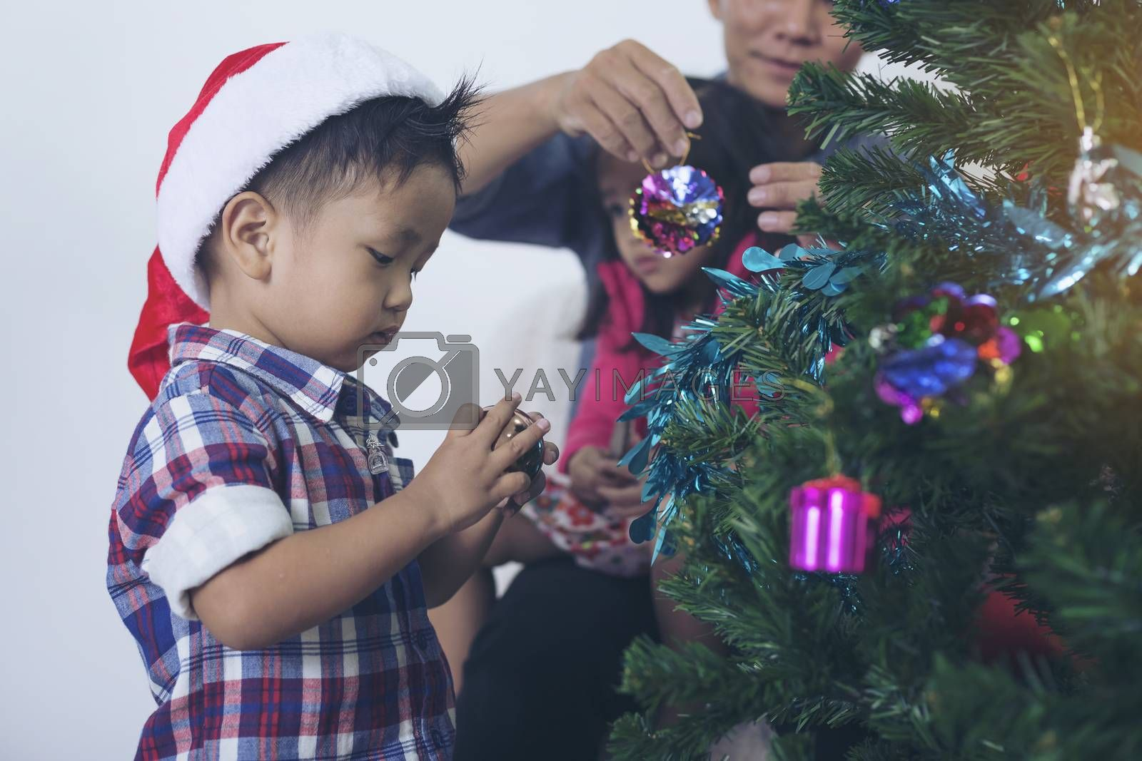 Father and son help to decorate the Christmas tree.