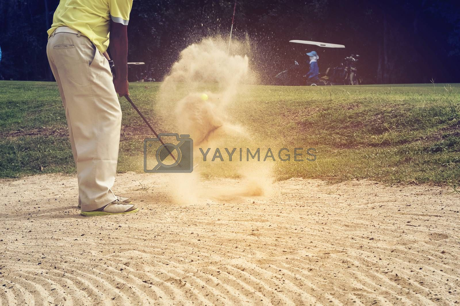 Golfer hitting the ball on the sand to stay on the green. Speeds Cause blurred by movement