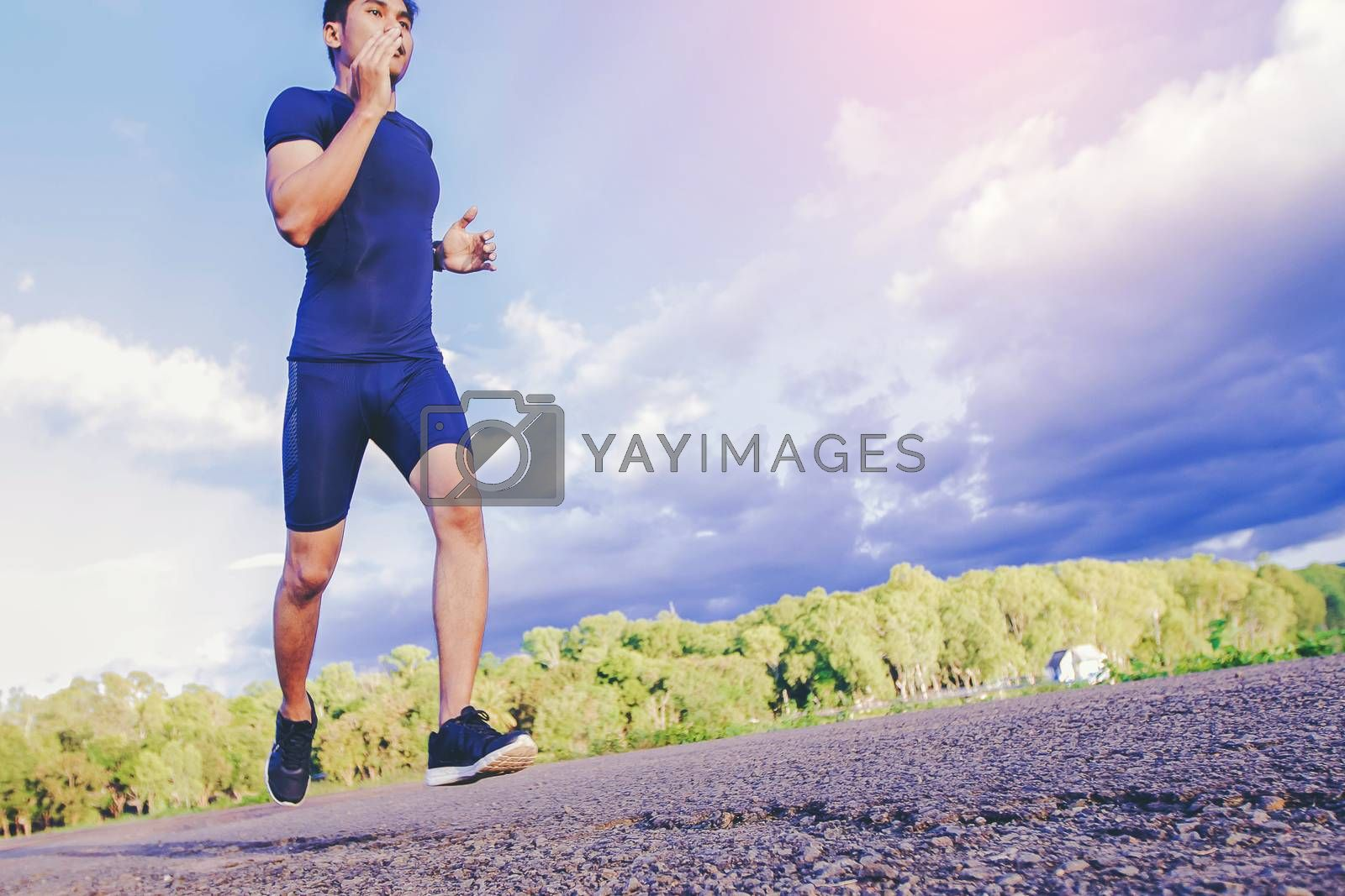 handsome man running on a rural road during sunset