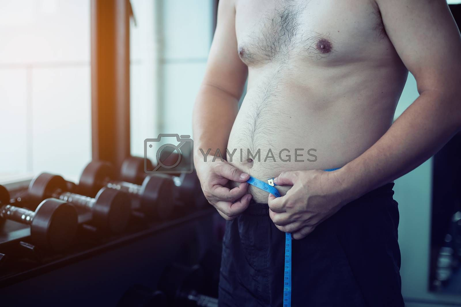 The young man measured his waist with a gauge after hard workouts. Health care concept