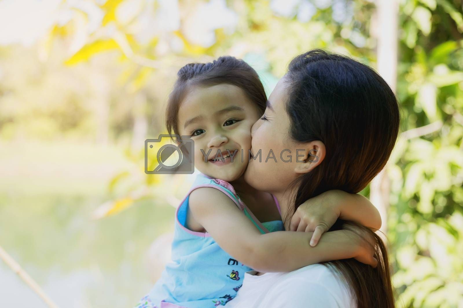 beautiful young mother and her daughter  in the park on a sunny summer day