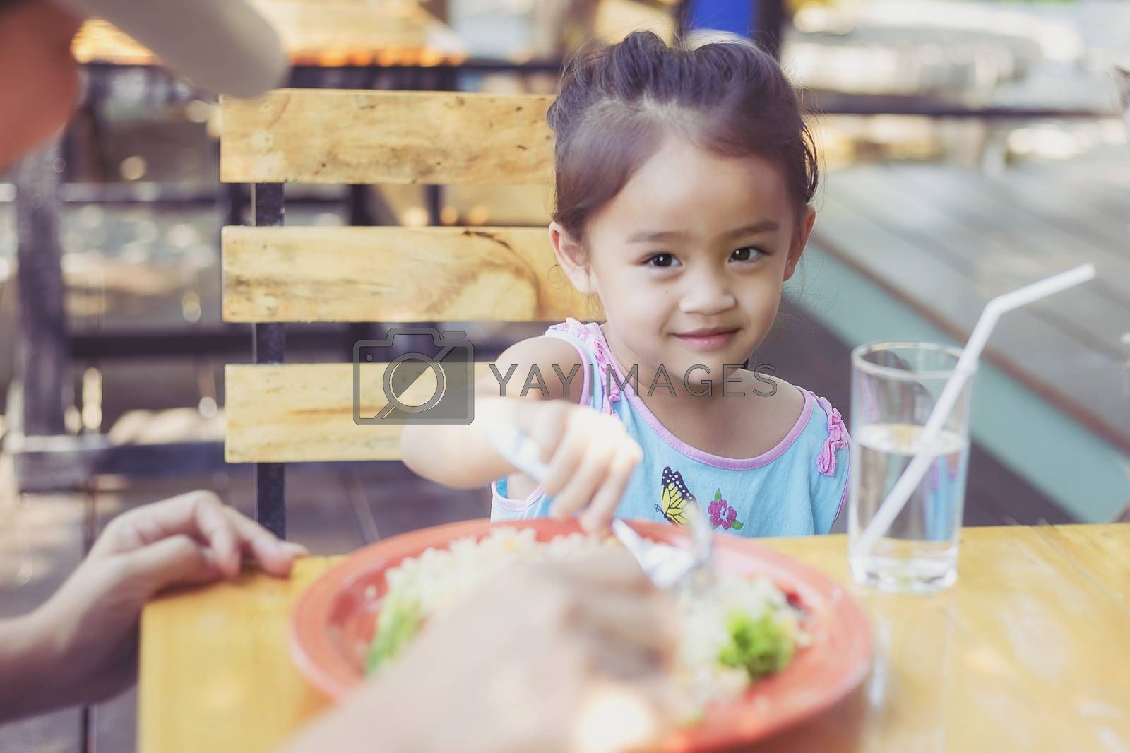 Close up Thai children eating in restaurant with her mother