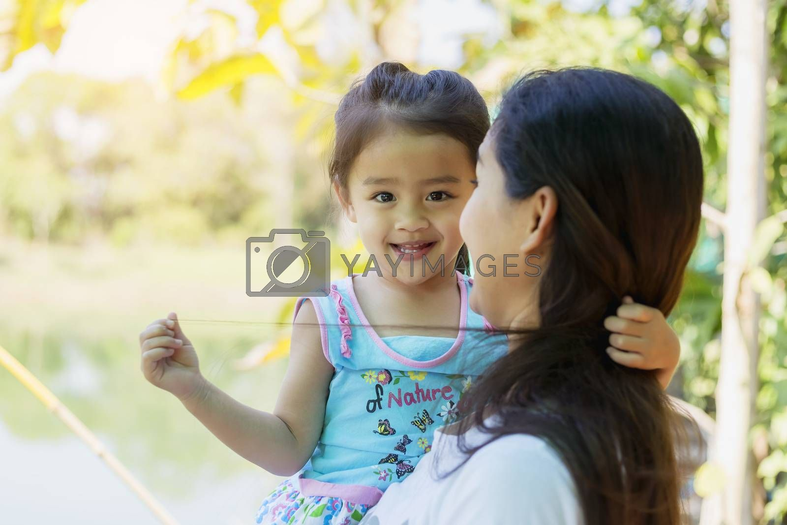 beautiful young mother and her daughter  in the park on a sunny  by numberone9018
