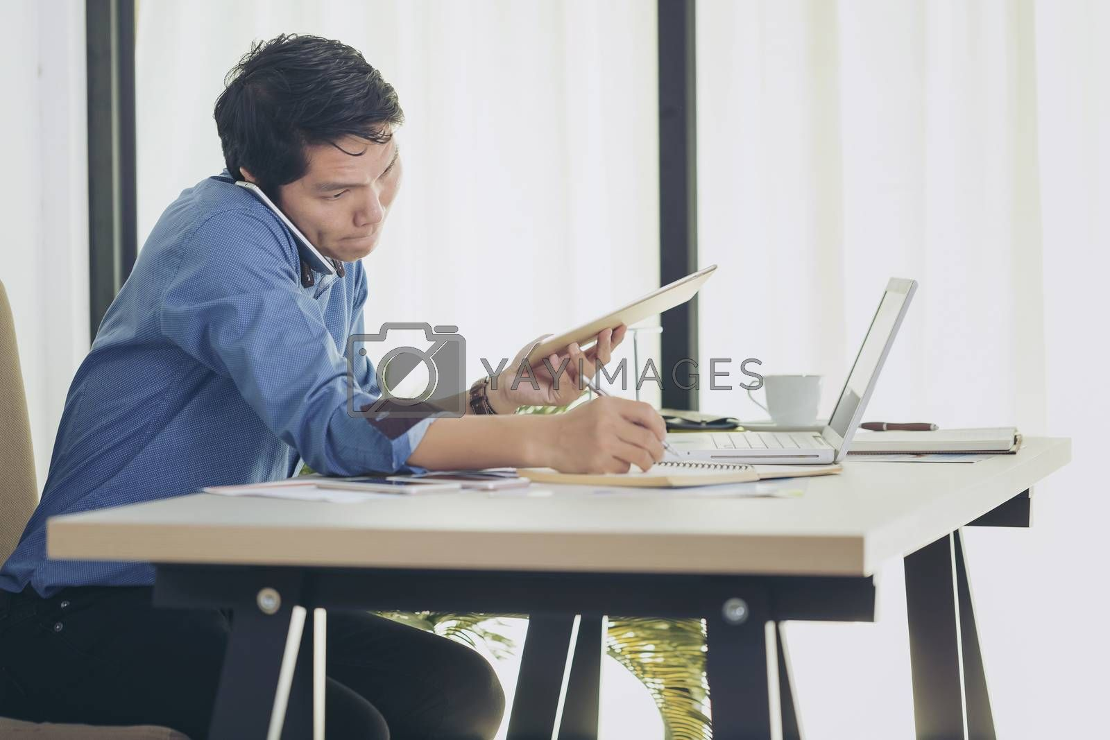 Busy businessman under stress due to excessive work. Serious focused businessman working on laptop computer online and many mobile phones.