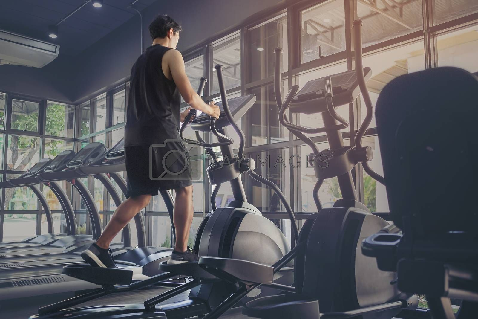 Young people running in machine treadmill at fitness gym club. Young sporty man and woman training in modern gym