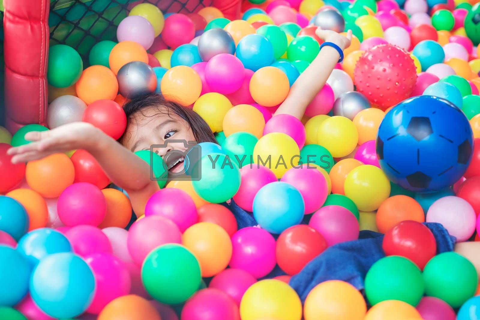 Happy little girl sitting in colourful balls. little girl with colored plastic balls. Funny child having fun indoors.
