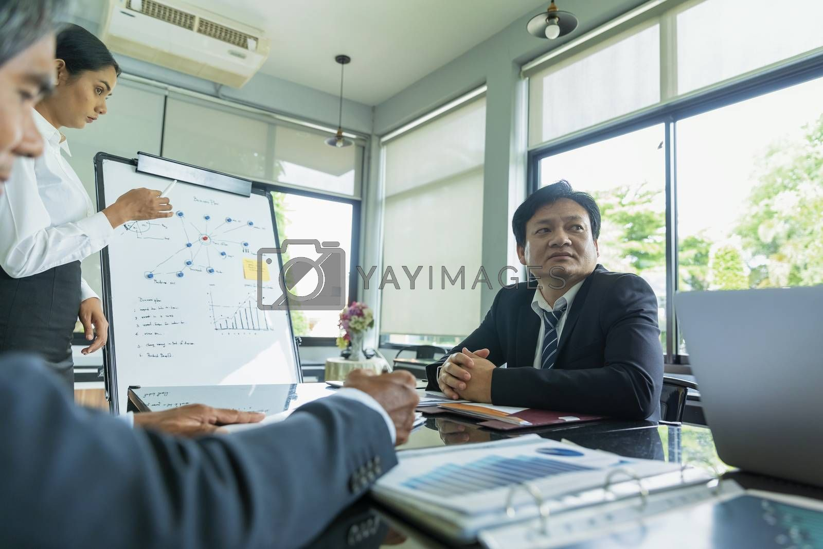 Handsome young businessman is describing a strategic plan to coworkers in conference room. Businessman explaining business plan to coworkers in conference room.