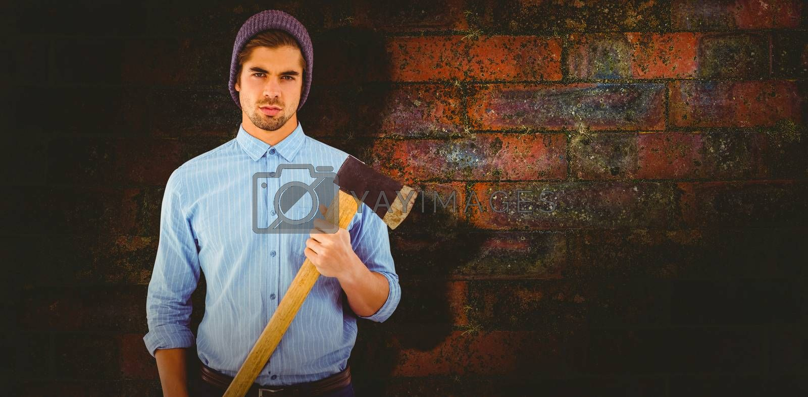 Portrait of serious hipster holding axe against texture of bricks wall