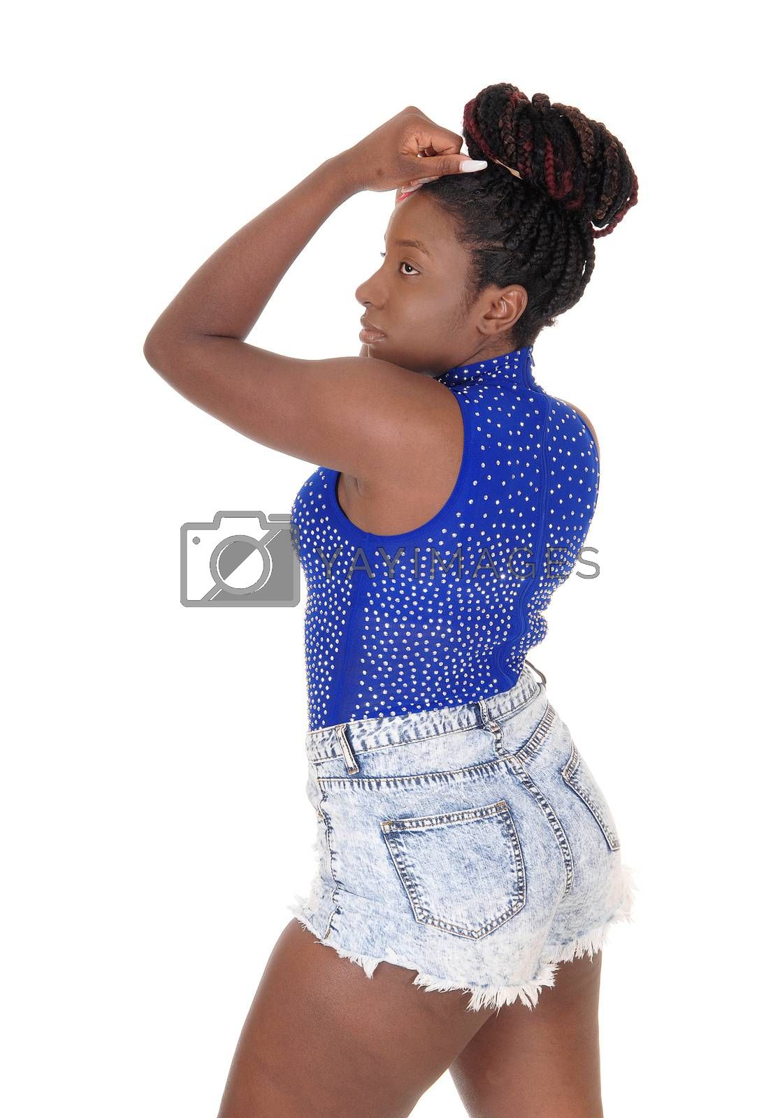 A beautiful tall African American woman standing in the studio in a blue top and jeans shorts, isolated for white background