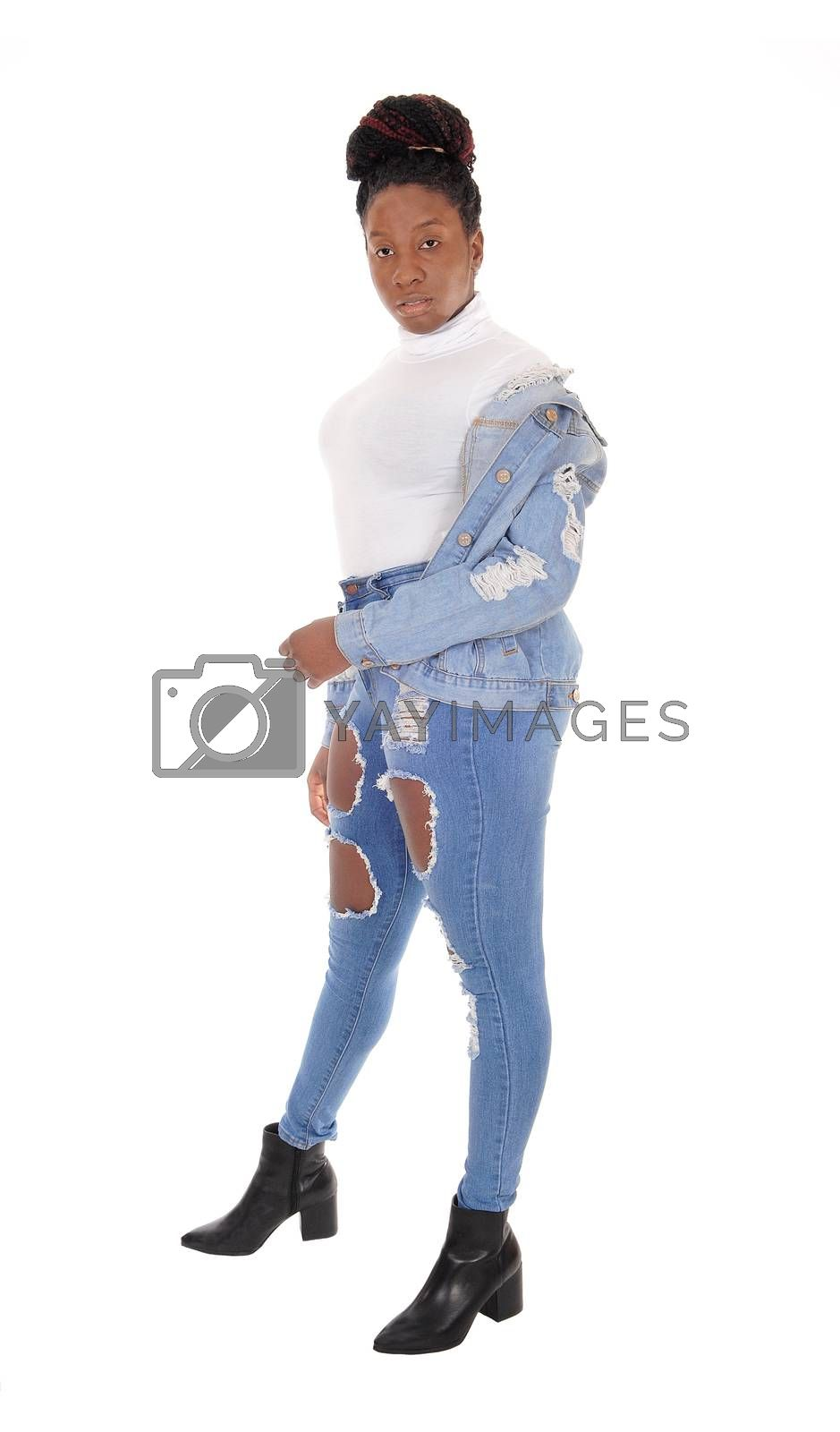 A young African American woman standing in ripped jeans with her jacket over her shoulder and white top, isolated for white background