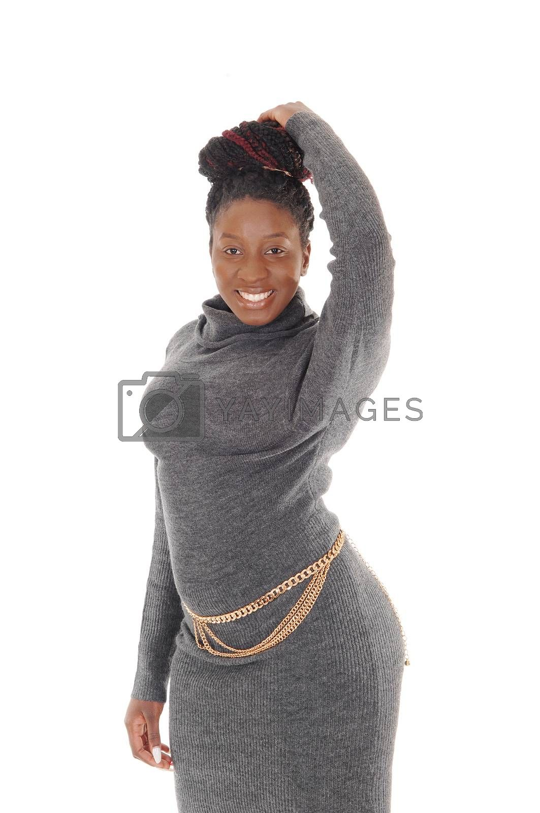 A beautiful young African American female standing in a tight gray dress, with one hand on her head, isolated for white background