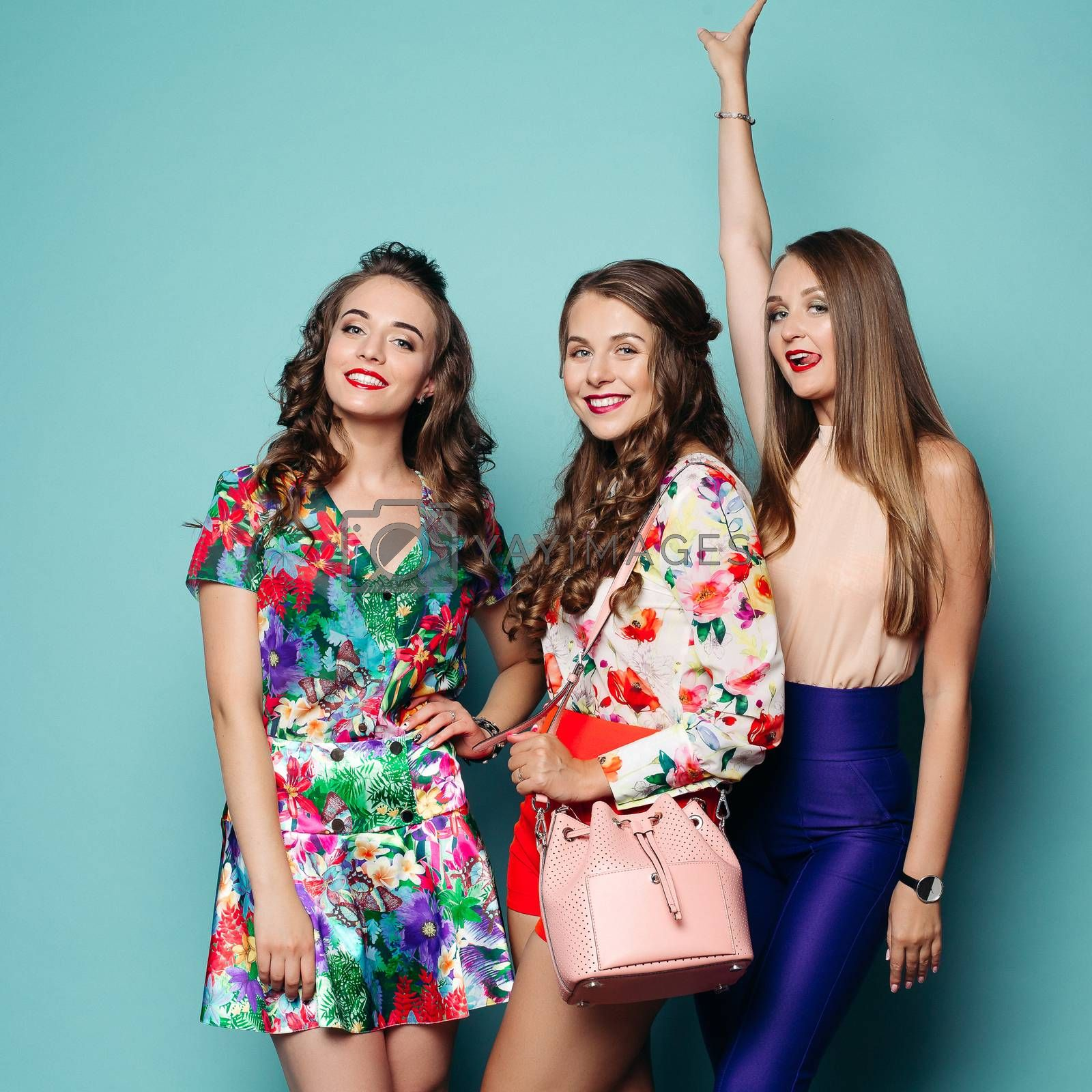 Studio portrait of pretty fashionable girlfriends in bright clothes posing at camera over blue background. Flowered dress, shirt and shorts with crossbag and slim girl in top and blue trousers with arm up sticking out tongue.