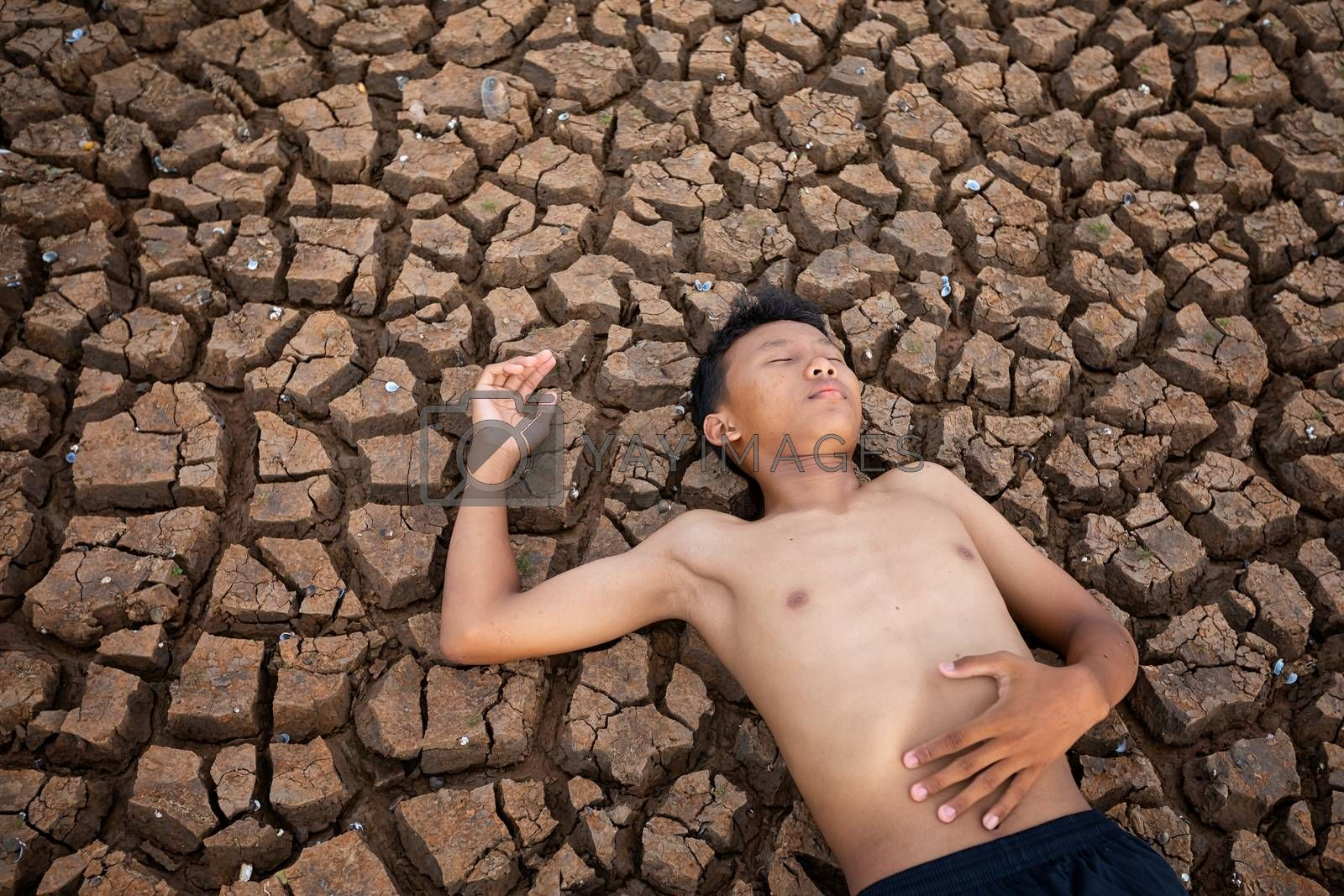 Sad a boy Lying  on cracked earth waiting for the hope of the sky to rain. Affected of global warming made climate change. Water shortage and drought concept.