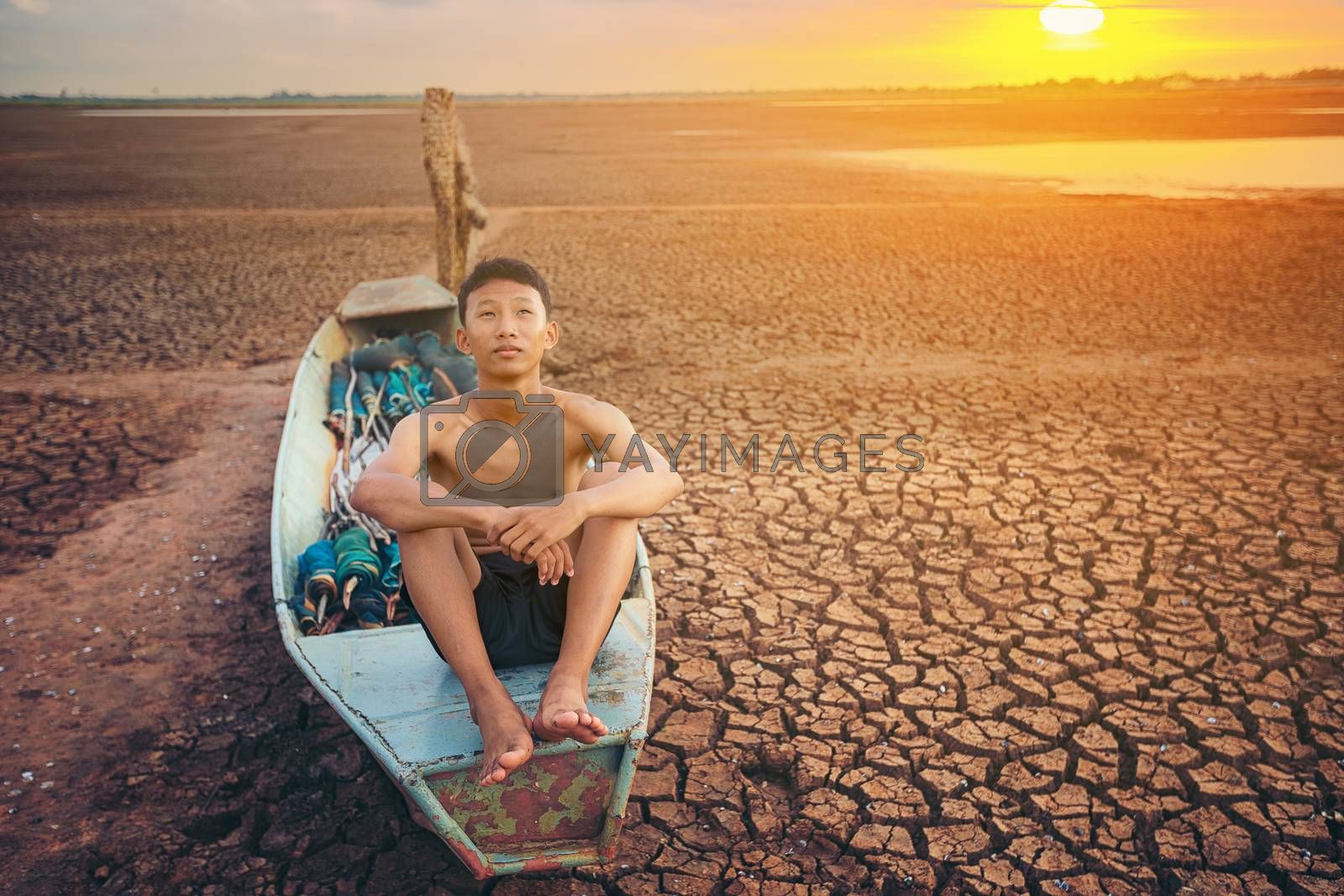 Sad a boy sitting on a boat that was parked in an arid ground for the hope of the sky to rain. Affected of global warming made climate change. Water shortage and drought concept.