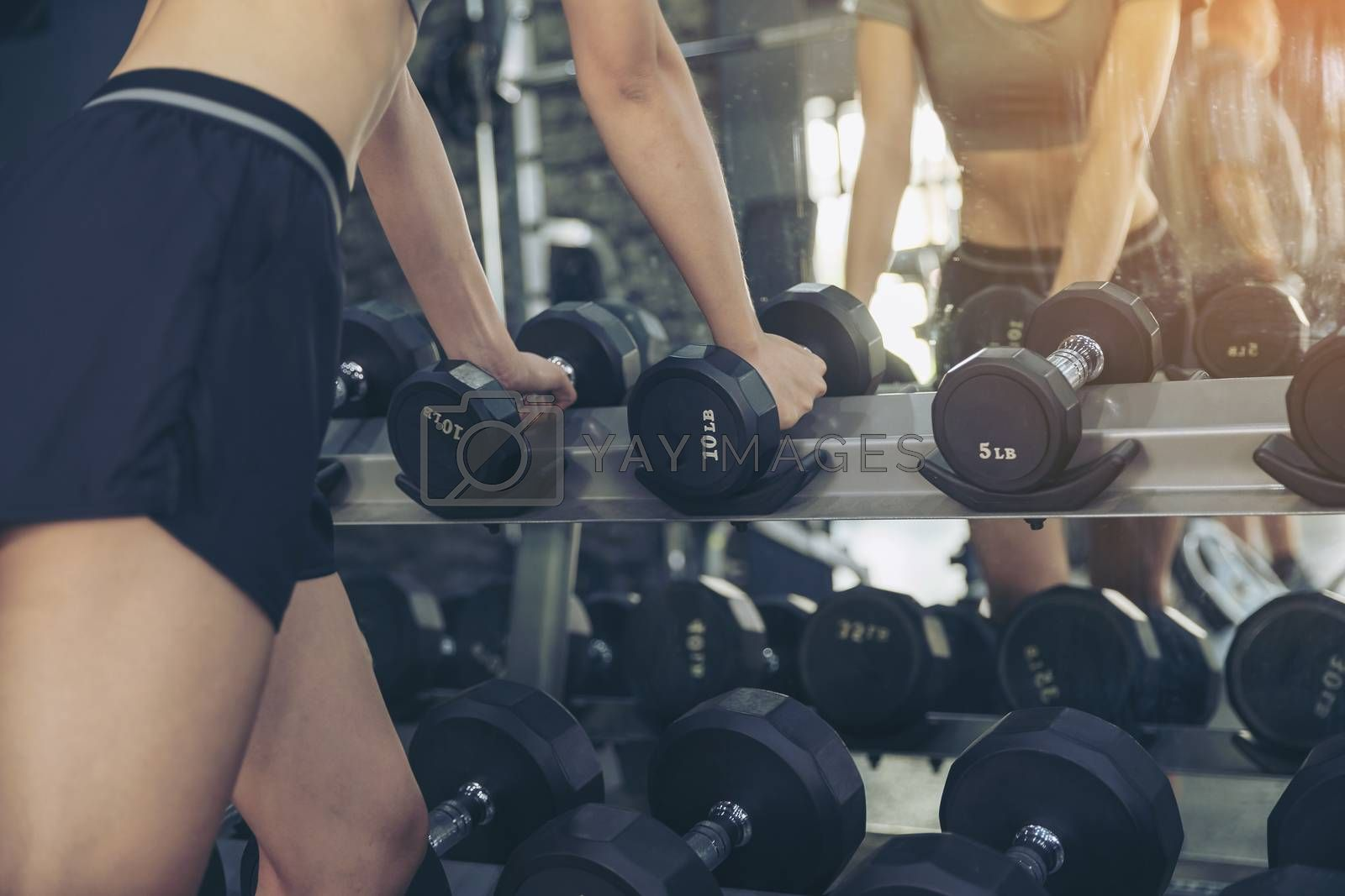 Close up of a beautiful woman reaching for a dumbbell to exercise in the gym