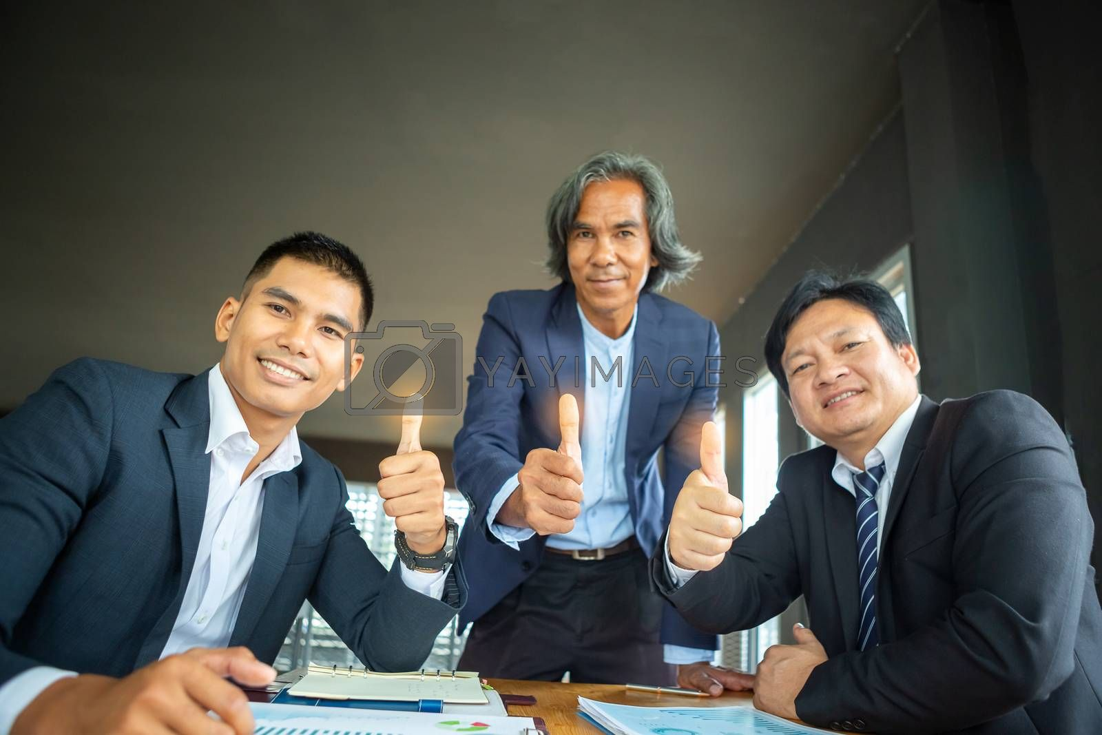 The three businessmen who thumbs up indicate the success of their business operations. Teamwork concept for development and success