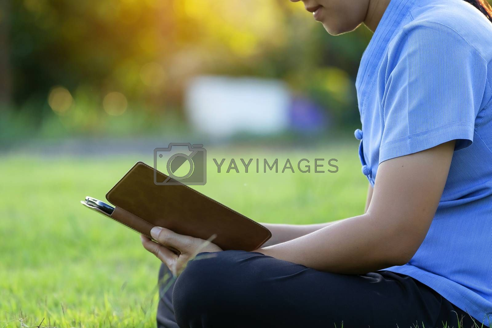 Portrait of beautiful young women who relax by watching the tablet in the lawn relax. Smiling Thai woman using digital tablet while lying in green spring garden