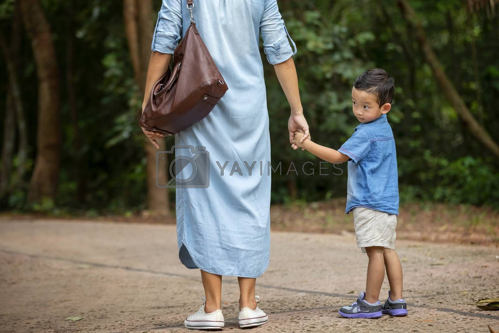 Happy mother and adorable little boy enjoying warm weather at beautiful park