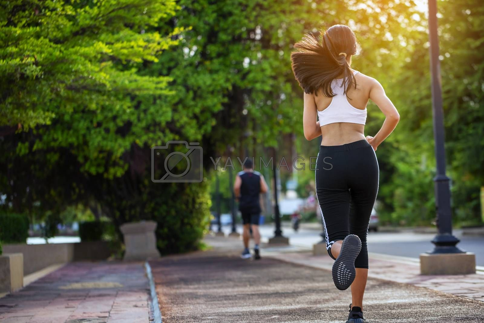Beautiful woman jogger outdoor living healthy lifestyle in city park. Concept sport and a healthy lifestyle in the city