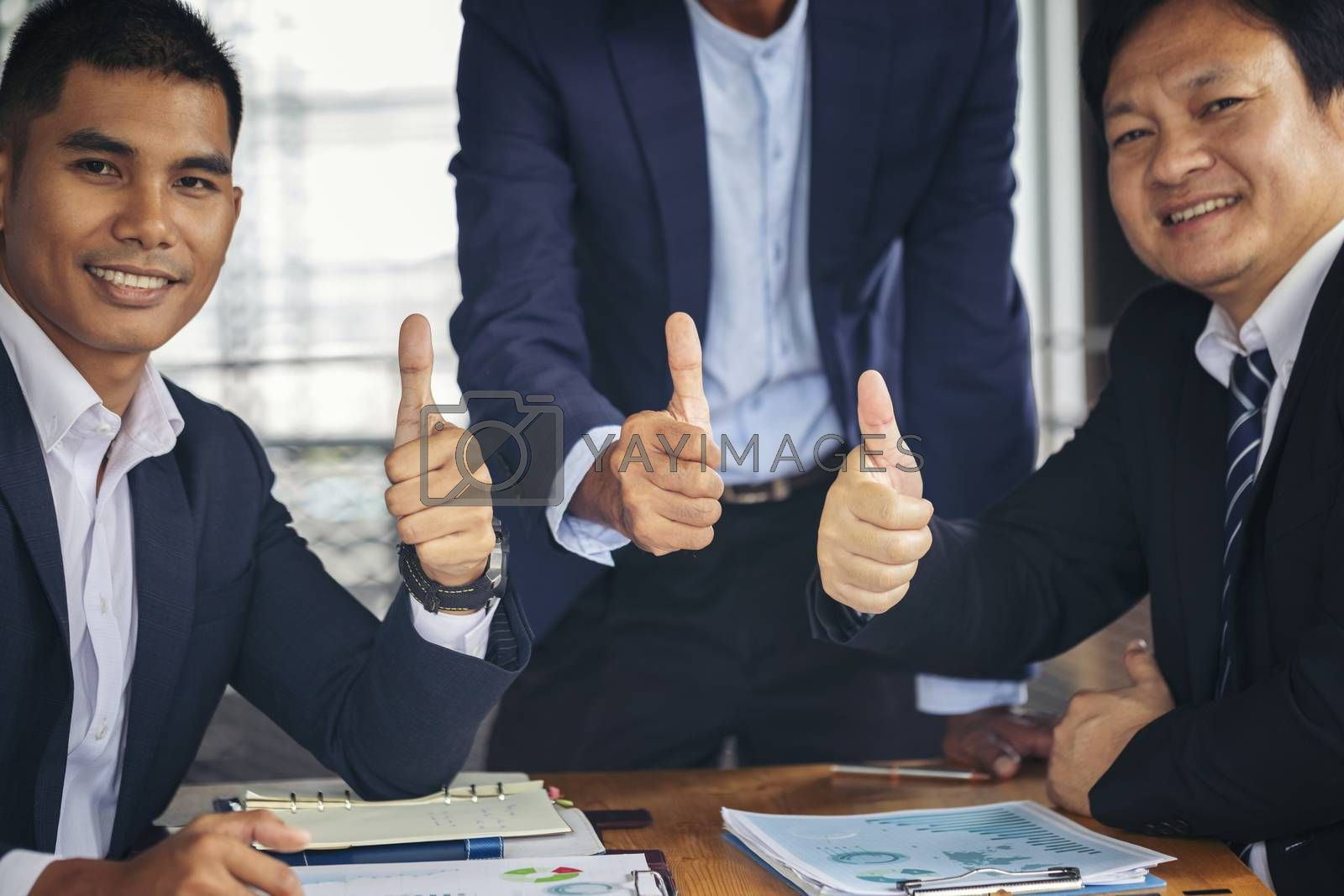 Three business partners keeping thumbs up. cheerful business group giving thumbs up