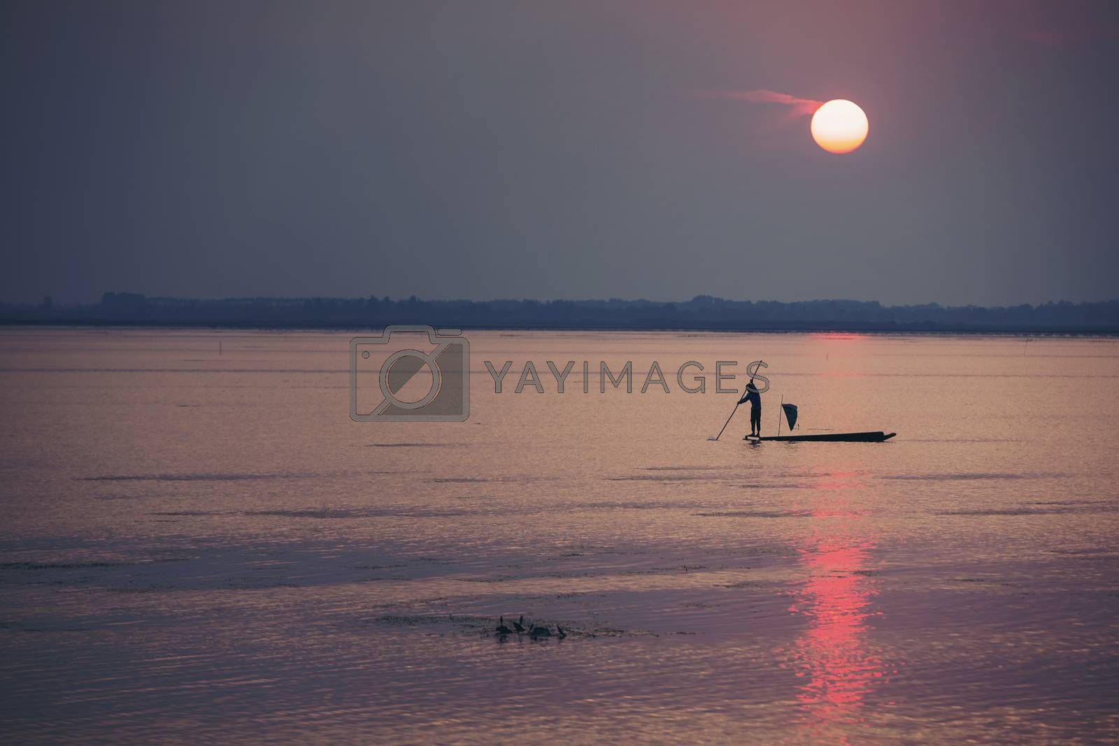 Fishermen make a living by using traps to catch fish that have nets like catching fish during the sunset.