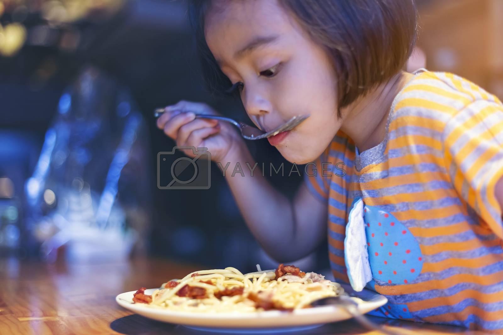 Asian little girl is eating spaghetti bolognese in the restaurant happily.