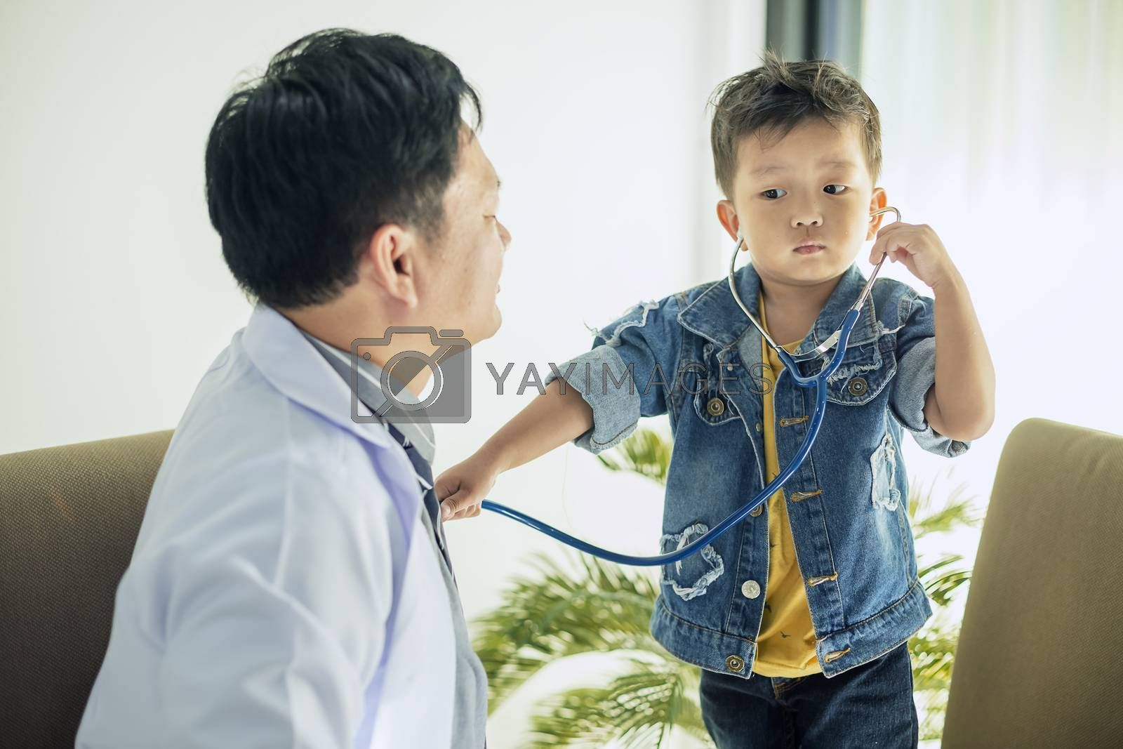 The image of a cute little boy goes to the doctor and is teasing the doctor using a stethoscope to listen to the doctor's heart.