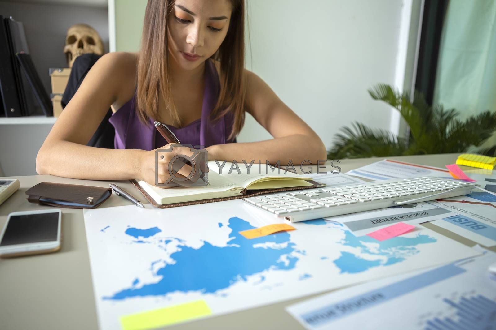 The image of a beautiful young business woman working tensely with a worksheet full of tables.