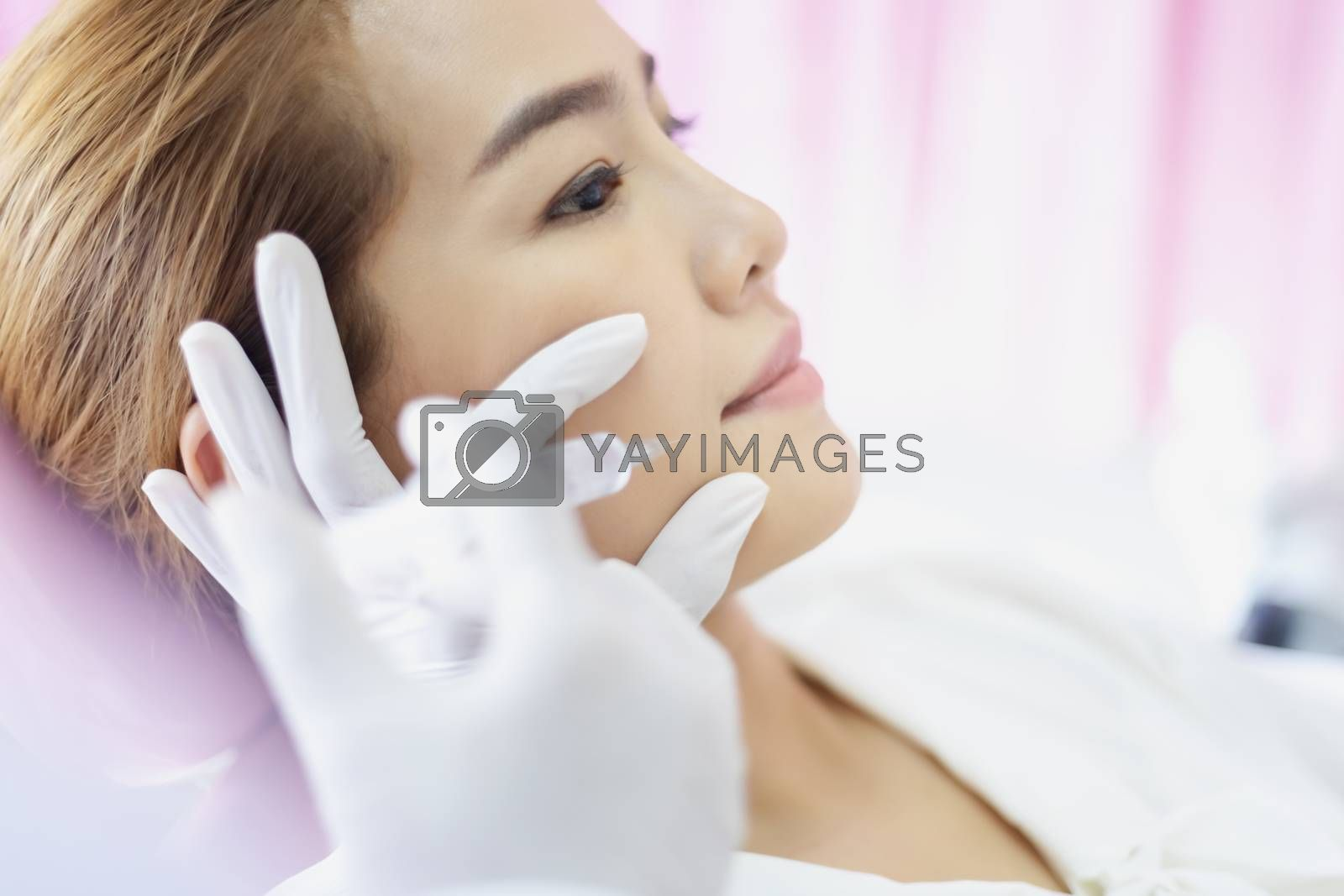 Beautiful women are injecting Botox in the face. The medical specialist is holding a syringe and injecting it on her forehead.