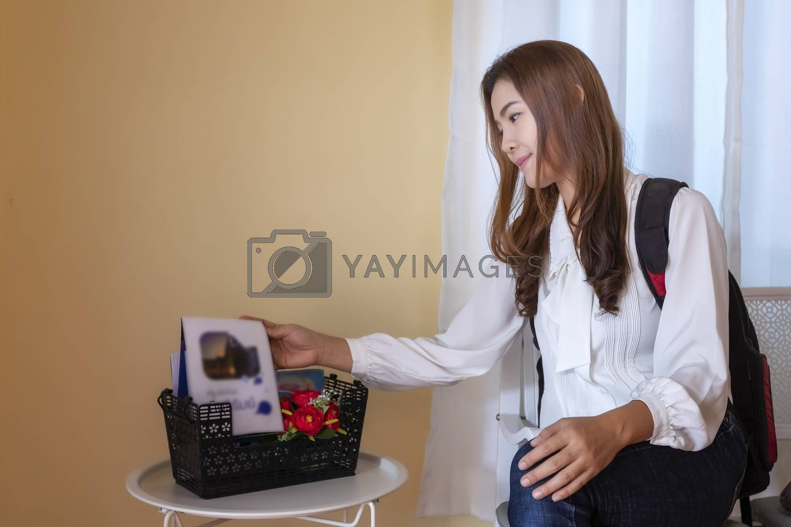 Beautiful young traveler is carrying a backpack to watch the brochures to plan her trip at the resort that she stayed.