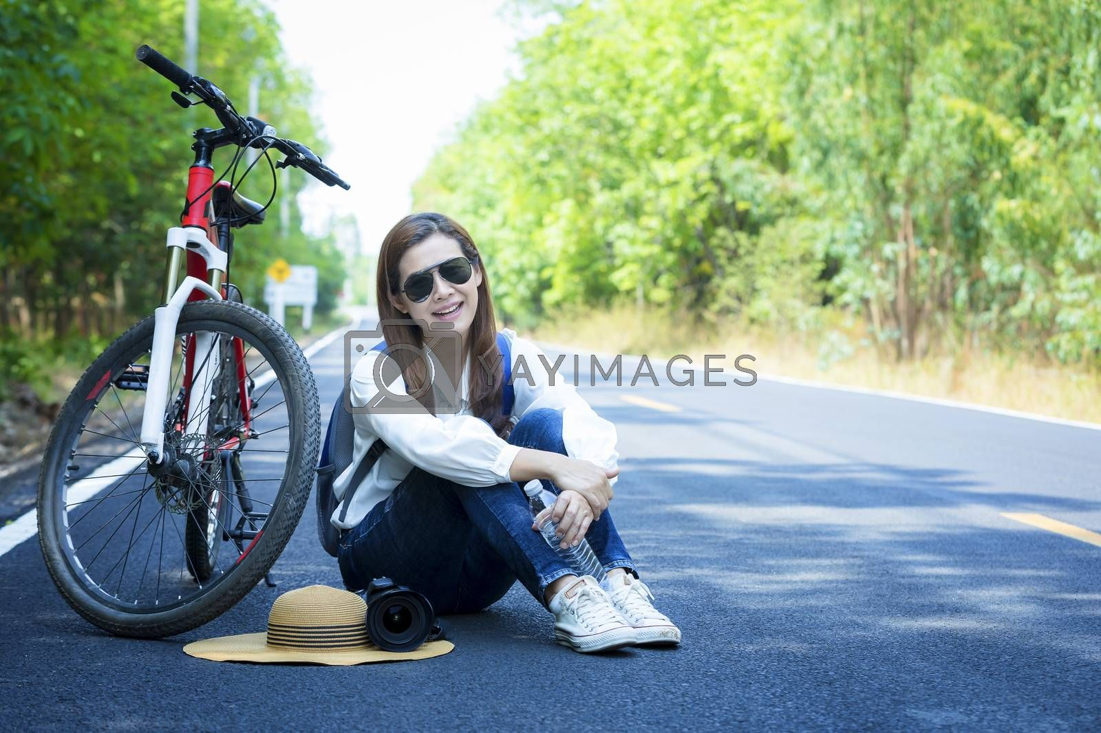 Beautiful woman sat on the side of the bicycle after biking to travel along the paved road on both sides of the road, full of beautiful green trees. The concept of travel and freedom.