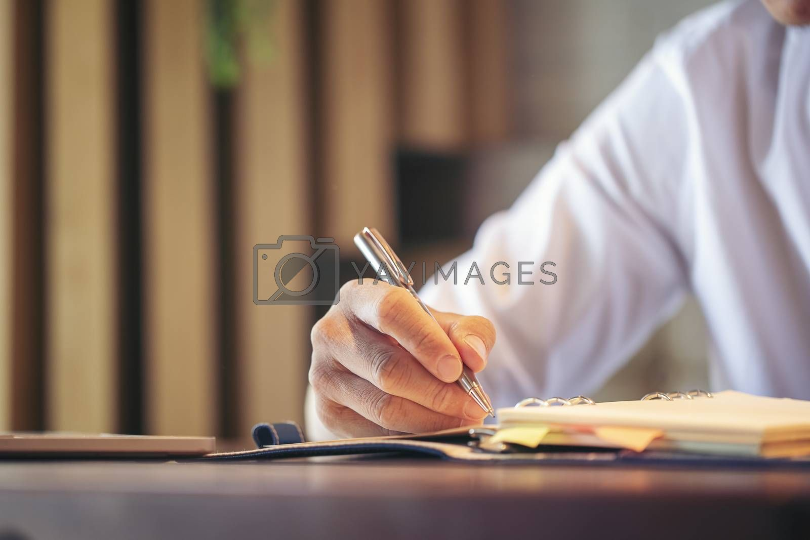 The handsome young businessman sat, planned and negotiated with the client with a mobile phone, with a somewhat stressful gesture in the hand, holding a note pen as the client wants.
