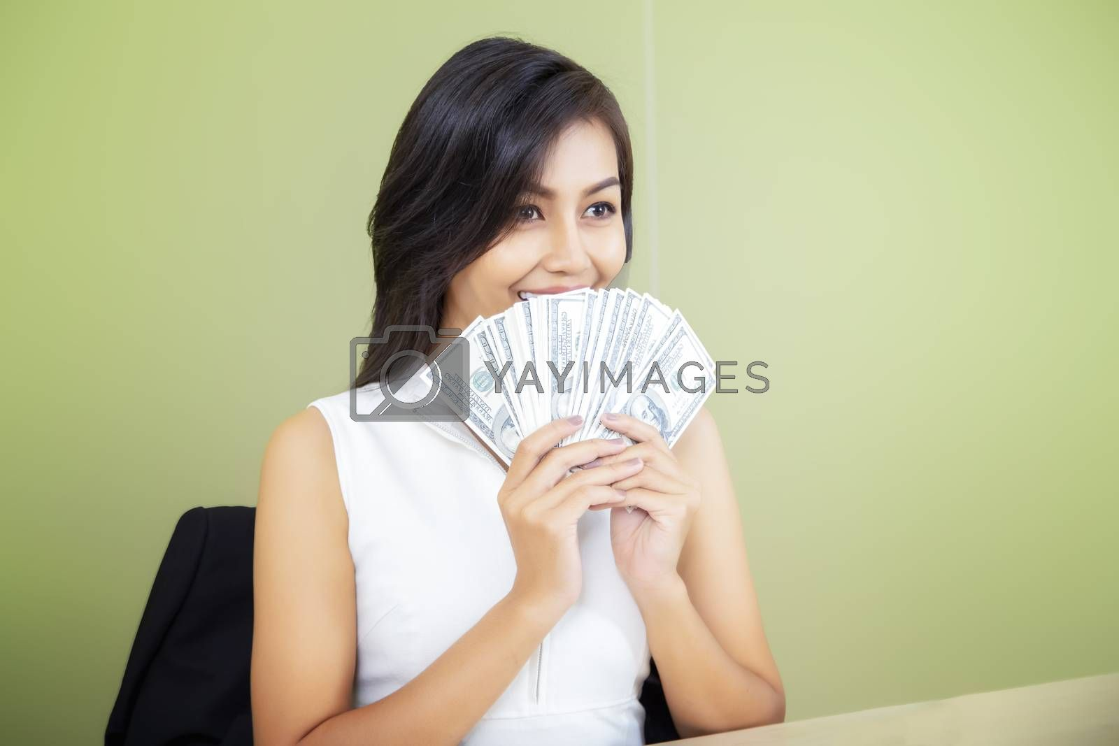 Cheerful attractive young smiling woman with dollars in hand And dreaming happily