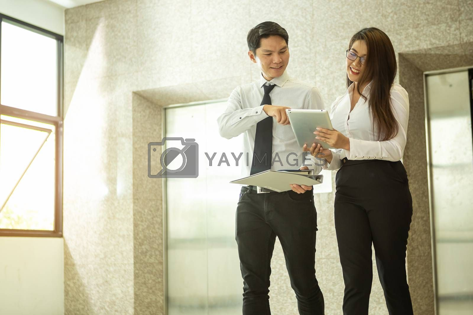 Two executives are talking to each other using a digital tablet  by numberone9018